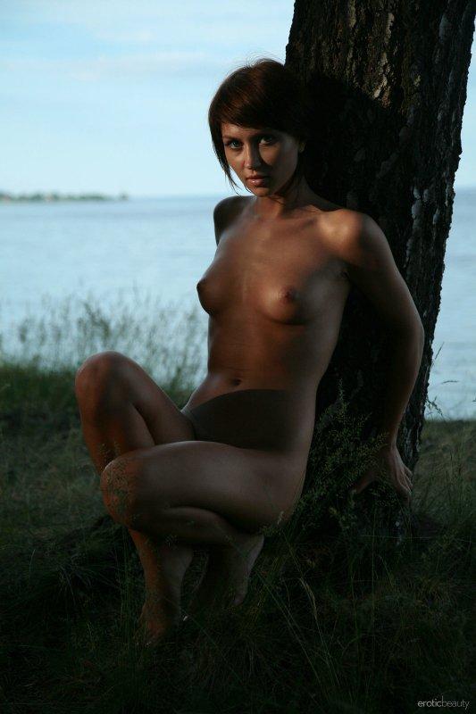 Голая девушка на закате на берегу озера