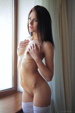 Голая брюнетка в белых чулках с красивым телом