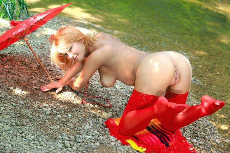 Голая девушка в красных чулках на природе