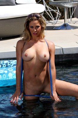 Голая женщина в бассейне показывает киску