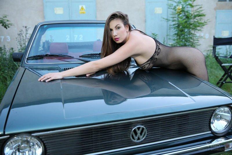 Знойная девушка с большой грудью позирует в машине