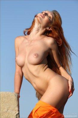 Голая рыжая красотка сексуально позирует на природе