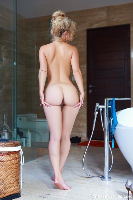 Стройная голая блондинка купается в ванной с пеной