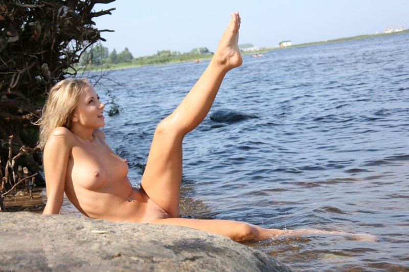 Красивая сексуальная блондинка с бритой киской на море