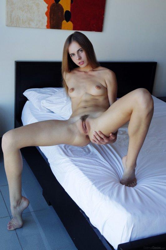 Молодая брюнетка полностью голая показывает киску