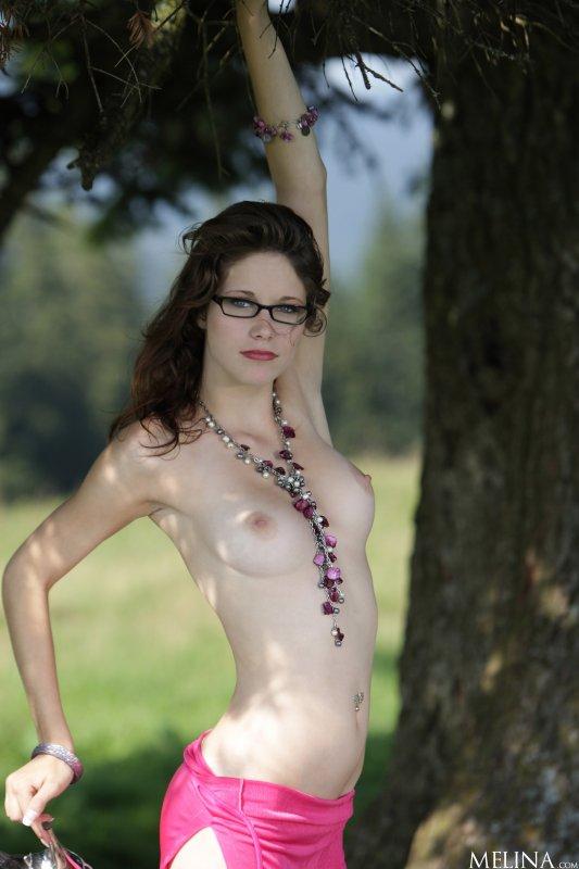 Голая стройная девушка в очках с упругими сиськами