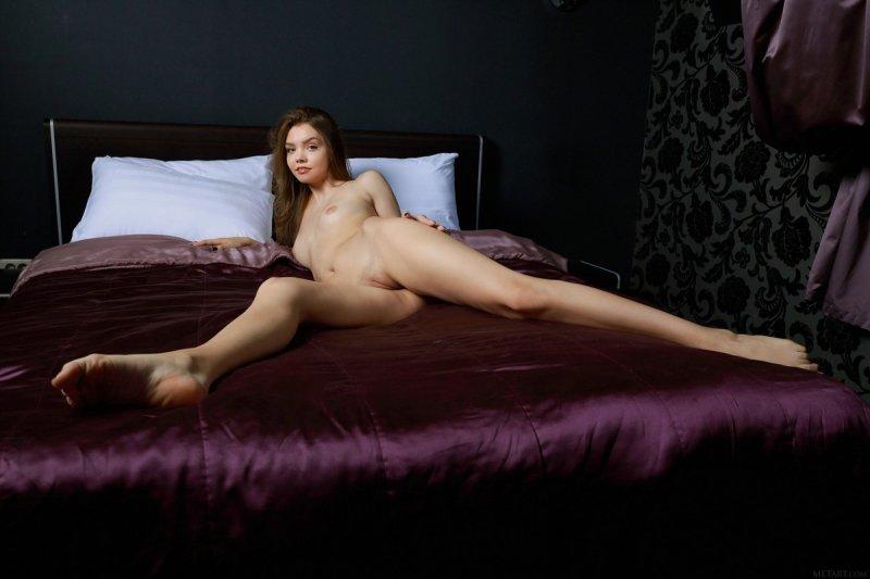 Молодая девушка с сексуальной попой позирует на кровати