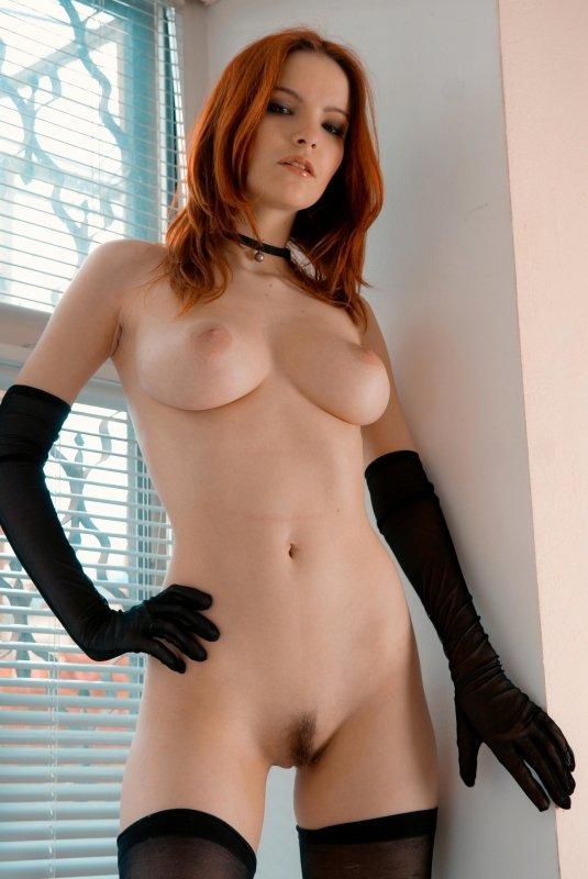 Русская рыжая девушка позирует в черных чулках