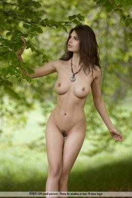 Зрелая женщина с большой грудью позирует в лесу