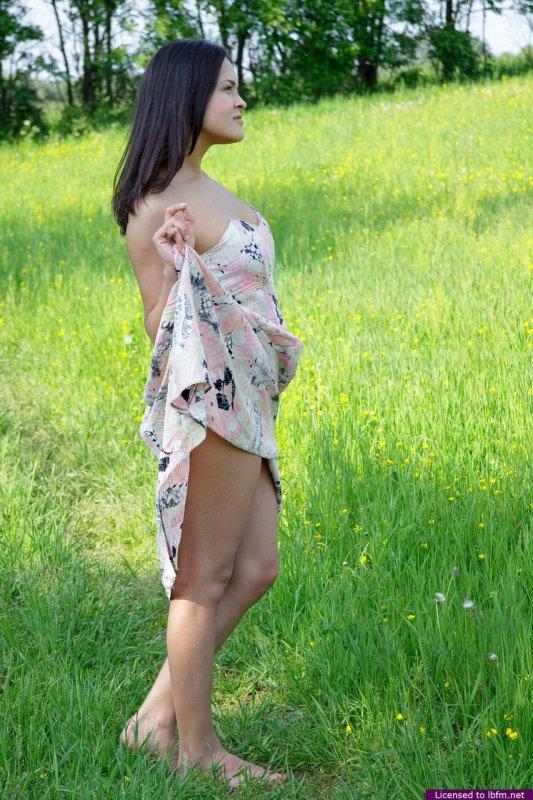Озорная азиатка показала голую попу на зеленой поляне