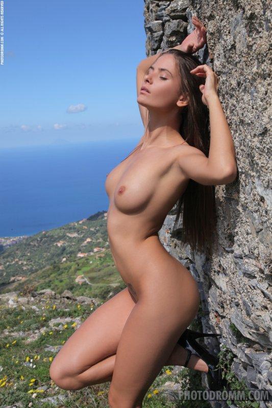 Красивая фигуристая брюнетка на природе крутит попкой