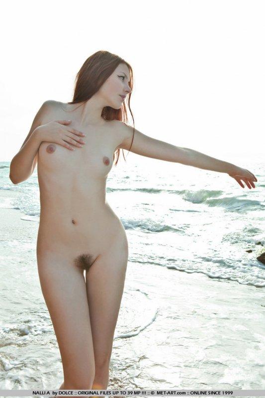 Стройная рыжая девушка на природе позирует в голом виде