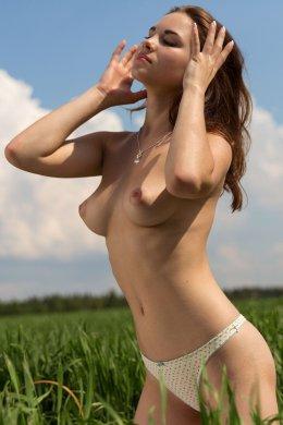 Молодая чика показала небольшую упругую грудь в поле