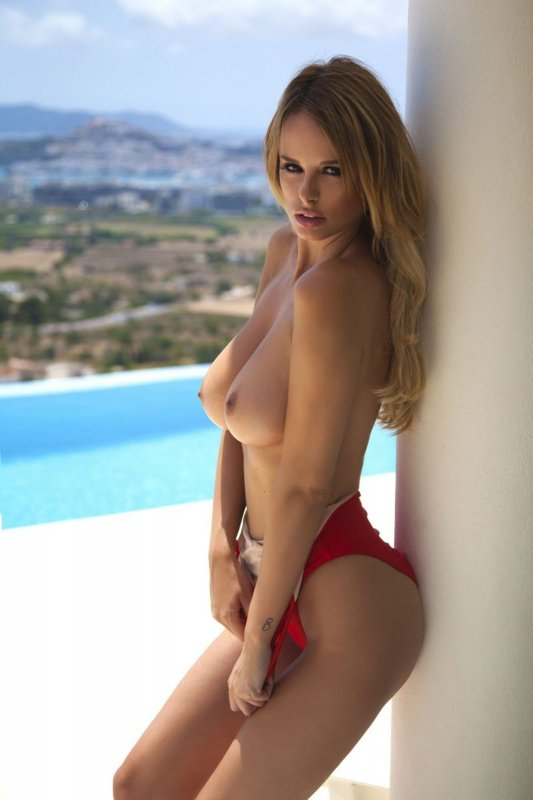 Блондинка с большой грудью позирует без купальника