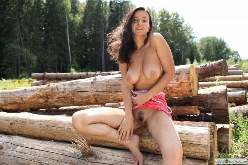 Оголенная брюнетка с интимной стрижкой на лесоповале