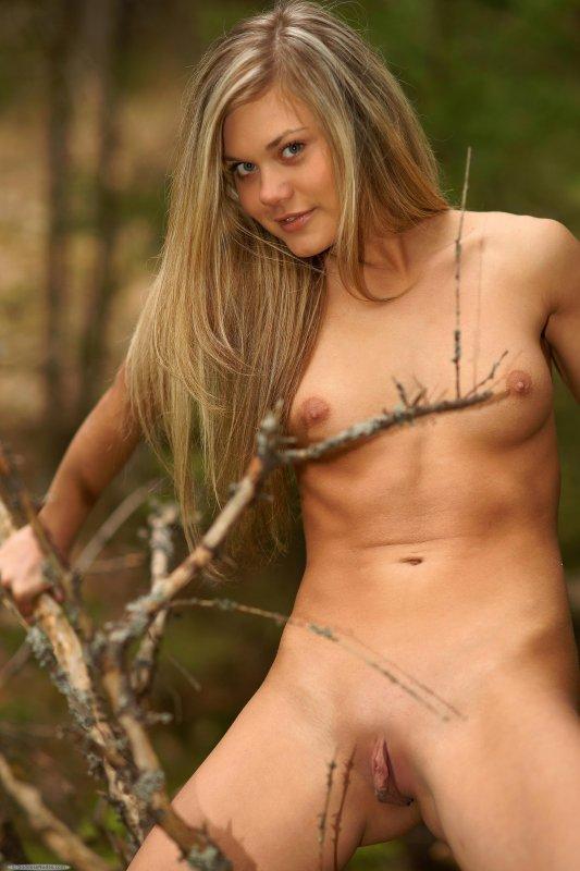 Белокурая стройная девушка игриво разделась в лесу