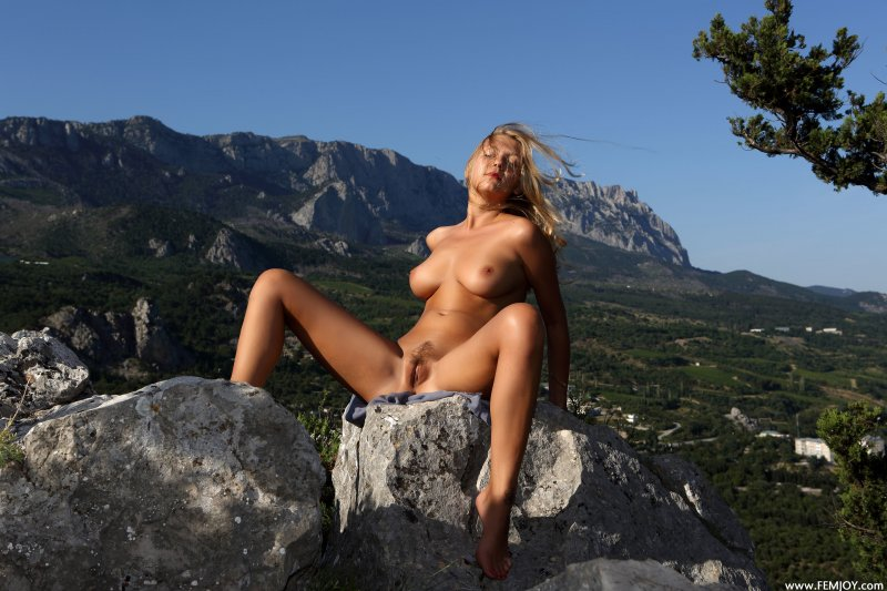 Голая стройная девушка в горах позирует обнаженной