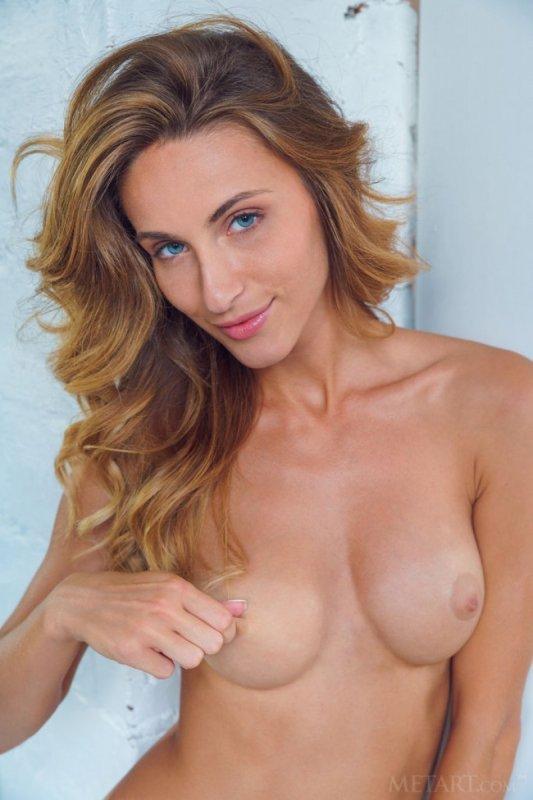 Стройная голая блондинка с голубыми глазами улыбается