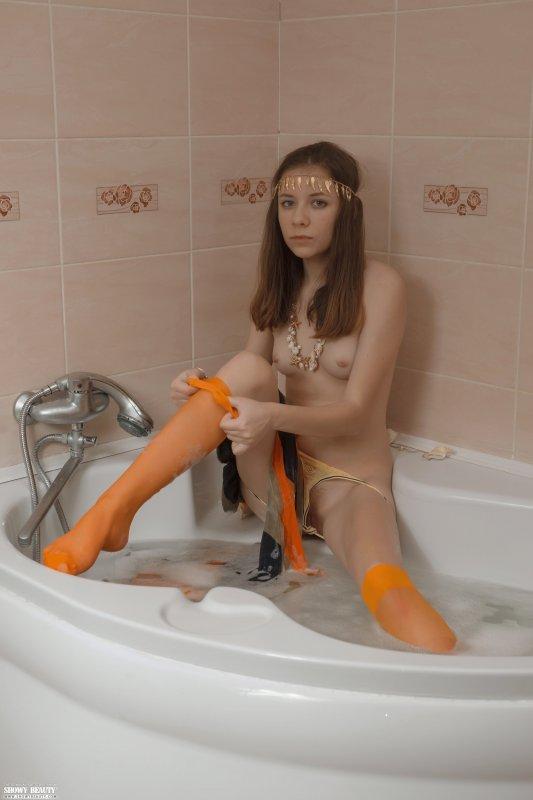 Рыжая девушка в ванной показала небольшую грудь и щелку