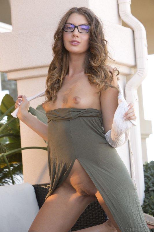 Молодая девушка в очках сексуально позирует во дворе