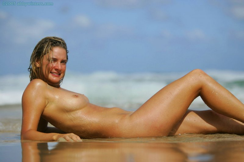 Обнаженная девушка на пляже дурачится и мило позирует