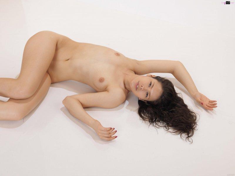 Стройная голая девушка на каблуках позирует в студии